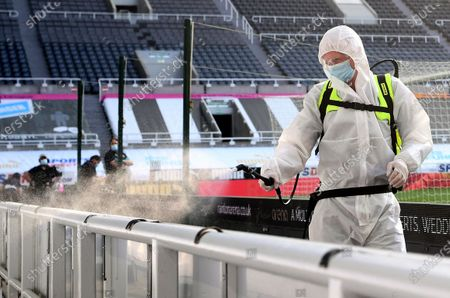The advertising boards are sprayed with a disinfectant at half-time during the English Premier League match between Newcastle United and Aston Villa in Newcastle, Britain, 24 June 2020.