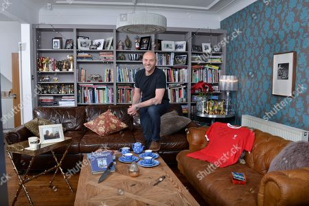 Stock Photo of Simon Rimmer 'My Haven'- Living room of his Manchester home 30.1.2018  1.DAD-S WATCH - My dad gave me this when I was about 16. I have always loved the look of it. It was a gift to my dad from his parents on his 21st. 2. FLO-S BOX - I have so many things the kids have made over the years, but there-s something I love about this box above many others. It-s 14 years old and wearing well. 3. LIVERPOOL SHIRT -Signed  4. GIRAFFE Collection - my Mum and Dad have one of these, they-ve had it for years. In my days of collecting bric a brac I found this one in a charity shop for 15p. I-ve got 10 of them now. 5. BLUE DOMINO TEA SET - I still collect the original stuff by T G Green. It-s harder and harder to find. Love the cobalt blue colour and the indented dots. 6. COFFEE MUG - This is possibly the ugliest mug in the world! I bought it from Peets Coffee (set up by the original owner of Starbucks) Filmore St San Francisco. 7.PAULA REGO - When Ali and I were first together, we went to an exhibition and fell in love with her work. Always promised ourselves if we could ever afford a piece we-d buy one. 8. BLOK KNIFE - The guys from Blok Knives were on Sunday Brunch recently and made this knife especially for me. I-ve always wanted a handmade knife and guard it with my life 9. CALIFORNIA PHOTO - Del Mar in San Diego is my happy place. This photo of Ali, the kids and me takes me back there every time I see it 10.SILVER RHINO- Given by the Army 11. COOK BOOK- Graham Kerr 'The Galloping Gourmet' Inspirational Chef that got him into cooking.