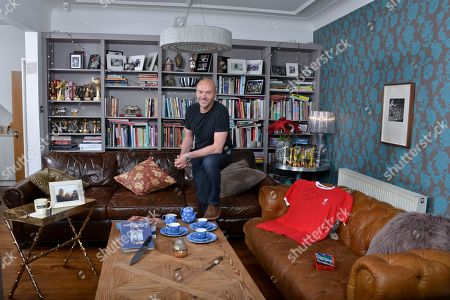 Stock Picture of Simon Rimmer 'My Haven'- Living room of his Manchester home 30.1.2018  1.DAD-S WATCH - My dad gave me this when I was about 16. I have always loved the look of it. It was a gift to my dad from his parents on his 21st. 2. FLO-S BOX - I have so many things the kids have made over the years, but there-s something I love about this box above many others. It-s 14 years old and wearing well. 3. LIVERPOOL SHIRT -Signed  4. GIRAFFE Collection - my Mum and Dad have one of these, they-ve had it for years. In my days of collecting bric a brac I found this one in a charity shop for 15p. I-ve got 10 of them now. 5. BLUE DOMINO TEA SET - I still collect the original stuff by T G Green. It-s harder and harder to find. Love the cobalt blue colour and the indented dots. 6. COFFEE MUG - This is possibly the ugliest mug in the world! I bought it from Peets Coffee (set up by the original owner of Starbucks) Filmore St San Francisco. 7.PAULA REGO - When Ali and I were first together, we went to an exhibition and fell in love with her work. Always promised ourselves if we could ever afford a piece we-d buy one. 8. BLOK KNIFE - The guys from Blok Knives were on Sunday Brunch recently and made this knife especially for me. I-ve always wanted a handmade knife and guard it with my life 9. CALIFORNIA PHOTO - Del Mar in San Diego is my happy place. This photo of Ali, the kids and me takes me back there every time I see it 10.SILVER RHINO- Given by the Army 11. COOK BOOK- Graham Kerr 'The Galloping Gourmet' Inspirational Chef that got him into cooking.