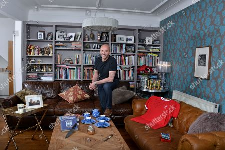 Stock Image of Simon Rimmer 'My Haven'- Living room of his Manchester home 30.1.2018  1.DAD-S WATCH - My dad gave me this when I was about 16. I have always loved the look of it. It was a gift to my dad from his parents on his 21st. 2. FLO-S BOX - I have so many things the kids have made over the years, but there-s something I love about this box above many others. It-s 14 years old and wearing well. 3. LIVERPOOL SHIRT -Signed  4. GIRAFFE Collection - my Mum and Dad have one of these, they-ve had it for years. In my days of collecting bric a brac I found this one in a charity shop for 15p. I-ve got 10 of them now. 5. BLUE DOMINO TEA SET - I still collect the original stuff by T G Green. It-s harder and harder to find. Love the cobalt blue colour and the indented dots. 6. COFFEE MUG - This is possibly the ugliest mug in the world! I bought it from Peets Coffee (set up by the original owner of Starbucks) Filmore St San Francisco. 7.PAULA REGO - When Ali and I were first together, we went to an exhibition and fell in love with her work. Always promised ourselves if we could ever afford a piece we-d buy one. 8. BLOK KNIFE - The guys from Blok Knives were on Sunday Brunch recently and made this knife especially for me. I-ve always wanted a handmade knife and guard it with my life 9. CALIFORNIA PHOTO - Del Mar in San Diego is my happy place. This photo of Ali, the kids and me takes me back there every time I see it 10.SILVER RHINO- Given by the Army 11. COOK BOOK- Graham Kerr 'The Galloping Gourmet' Inspirational Chef that got him into cooking.