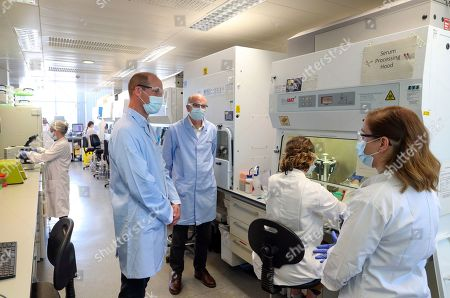 Stock Photo of Prince William wears a mask as he meets scientists, including Christina Dold (right), during a visit to the manufacturing laboratory where a vaccine against COVID-19 has been produced at the Oxford Vaccine Group's facility at the Churchill Hospital in Oxford. Trials began on 23rd April, with ten thousand people across the UK in the process of being vaccinated in the latest study to assess the potential success of the treatment, with the UK Government providing £84 million for the University of Oxford to develop and manufacture its coronavirus vaccine.