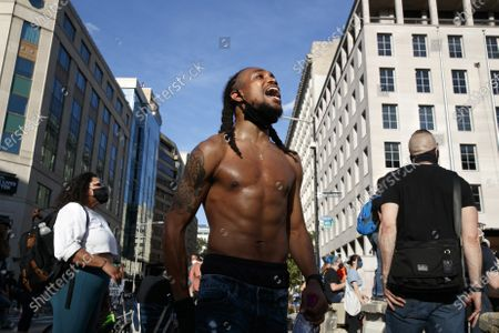 Aaron Covington of St. Louis, center, leads people in a chant as demonstrators protest in front of a police line on a section of 16th Street that's been renamed Black Lives Matter Plaza, in Washington, over the death of George Floyd, a black man who was in police custody in Minneapolis. Floyd died after being restrained by Minneapolis police officers