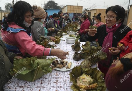 Stock Image of Women of the Shipibo Conibo ethnic group eat a dish called Juanes, made with rice wrapped in banana leaves, during the celebration of San Juan, the patron saint of the Peruvian Amazon, in the Cantagallo neighborhood of Lima, Peru, . The neighborhood reopened about 10 days ago after it had been under strict quarantine due to an outbreak of COVID-19