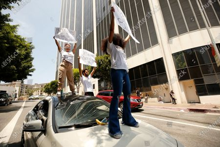 Payton Martin, left, and Vanessa Martinez, right, stand on top of a Mercedes as they join members of Black Lives Matter-Los Angeles and their supporters during a demonstration outside LAUSD headquarters during the School Board Zoom meeting to demand that the Board of Education defund school police, reallocating funds to other student-serving initiatives.