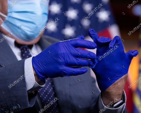 Stock Picture of United States Representative G. K. Butterfield (Democrat of North Carolina) puts on protective gloves prior to a news conference at the United States Capitol in Washington D.C., U.S.,.