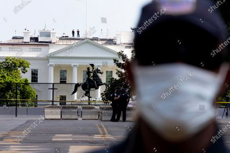 A police officer is seen standing at a police line in front of the view of a fence put up around closed-off Lafayette Park across the street from the White House, in Washington DC, USA, 24 June 2020. Police used chemical agents to clear out Lafayette Park and skirmishes broke out between protesters and police, 22 June. Since then police have pushed the police line back to include a block of Black Lives Matter Plaza. The death of George Floyd while in Minneapolis police custody has sparked global protests demanding justice and racial equality.