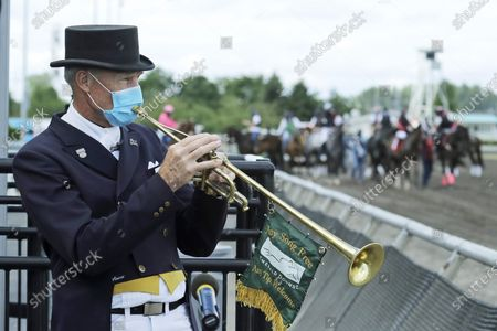 Track bugler Dan Harrington plays through a hole cut in his face mask, before a race at Emerald Downs Racetrack in Auburn, Wash., on the first day of thoroughbred horse racing at the track since all professional sports in Washington state were curtailed in March by the outbreak of the coronavirus. No spectators were allowed, but online wagering was available and the races were streamed. Organizers hope to continue racing into October on a modified schedule