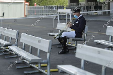 Stock Image of Track bugler Dan Harrington warms up, before a race at Emerald Downs Racetrack in Auburn, Wash., on the first day of thoroughbred horse racing at the track since all professional sports in Washington state were curtailed in March by the outbreak of the coronavirus. No spectators were allowed, but online wagering was available and the races were streamed. Organizers hope to continue racing into October on a modified schedule