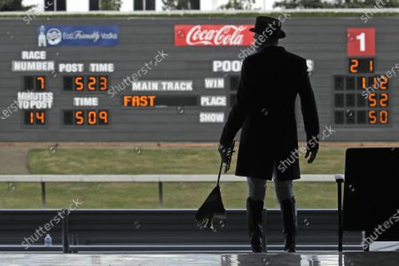 Track bugler Dan Harrington stands near empty seats, before playing just before a race at Emerald Downs Racetrack in Auburn, Wash., on the first day of thoroughbred horse racing at the track since all professional sports in Washington state were curtailed in March by the outbreak of the coronavirus. No spectators were allowed, but online wagering was available and the races were streamed. Organizers hope to continue racing into October on a modified schedule
