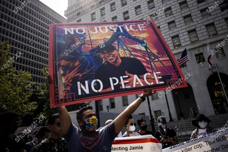 A protester holds a placard with a portrait of Andres Guardado during a Black Lives Matter protest outside the Hall of Justice in Los Angeles, California, USA, 24 June 2020. Guardado, an 18-year-old Salvadoran American, was fatally shot by a Deputy Sheriff in Los Angeles on 18 June 2020.