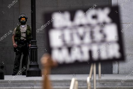An officer stands guard during a Black Lives Matter protest outside the Hall of Justice in Los Angeles, California, USA, 24 June 2020. The death of George Floyd while in Minneapolis police custody on 25 May has sparked global protests demanding justice and racial equality.
