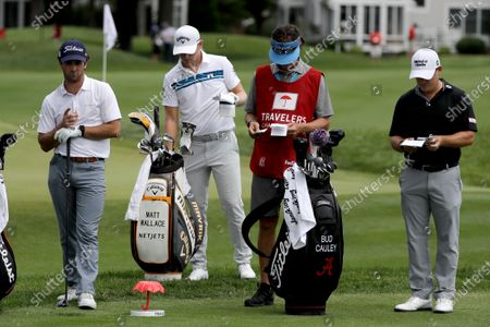 In this Thursday, June 25, photo, Denny McCarthy, left, Matt Wallace, center left, Bud Cauley, right, and Cauley's caddie Matt Hauser stand at the third tee box during the first round of the Travelers Championship golf tournament at TPC River Highlands in Cromwell, Conn. McCarthy told Golfchannel.com that he withdrew from the tournament after feeling sick Thursday night and testing positive for the coronavirus on Friday. Cauley, who played with McCarthy on Thursday, also withdrew before Friday's second round. McCarthy became the third PGA Tour player to test positive for the virus since its restart and the second this week, joining Cameron Champ who withdrew on Tuesday. Nick Watney withdrew just before the second round of last week's RBC Heritage Championship
