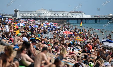 People soak up the sun on Brighton beach in Brighton, Britain, 25 June 2020. Temperatures of 33C have brought people to the beaches and parks as Britain continues to ease its lockdown. British Prime Minister Boris Johnson has  changed the two metre distancing rules from two meters to one. Pubs, galleries and cinemas can reopen their doors from 04 July. Countries around the world are taking increased measures to stem the widespread of the SARS-CoV-2 coronavirus which causes the Covid-19 disease.