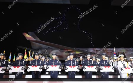 Drones fly in form to create an image depicting the silhouette of a saluting soldier as honor guards stand with caskets containing the remains of South Korean soldiers killed during the Korean War during a ceremony to mark the 70th anniversary of the outbreak of the 1950-53 conflict, at Seoul Air Base in Seongnam, south of Seoul, South Korea, 25 June 2020. The 1950 operation, commanded by US Gen. Douglas MacArthur, turned the tide of the war against the invading North Korea.
