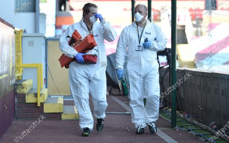 Medical staff wearing protective suits walks by pitch side ahead of the English Premier League soccer match between Burnley and Watford in Burnley, Britain, 25 June 2020.