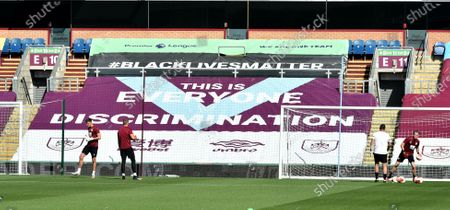 Burnley goalkeepers warm up in front of a Black Lives Matter banner ahead of the English Premier League soccer match between Burnley and Watford in Burnley, Britain, 25 June 2020.
