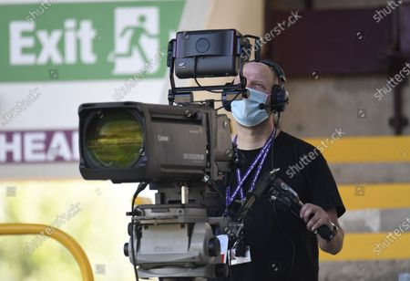 A TV camera operator wears a protective face mask ahead of the English Premier League soccer match between Burnley and Watford in Burnley, Britain, 25 June 2020.