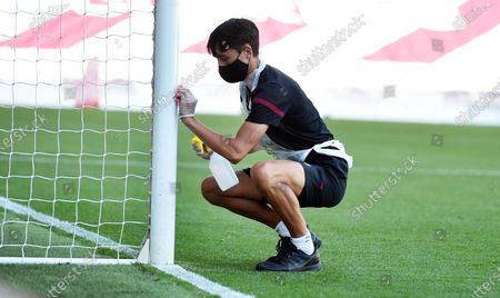 A member of staff cleans the goal post during the English Premier League match between Burnley and Watford in Burnley, Britain, 25 June 2020.