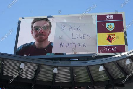 """A Burnley supporter shows a placard """"Black lives matter"""" on giant screen ahead of the English Premier League match between Burnley and Watford in Burnley, Britain, 25 June 2020."""