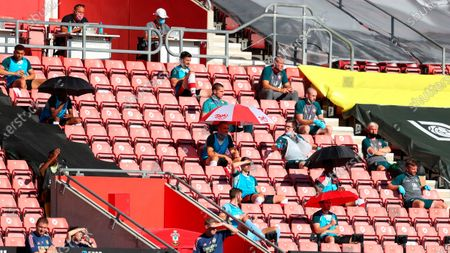 Southampton substitute players holding umbrellas to shade from the sun respect social distancing during the English Premier League soccer match between Southampton FC and Arsenal FC in Southampton, Britain, 25 June 2020.