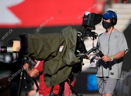 A tv cameraman wears a protective face mask during the English Premier League soccer match between Southampton FC and Arsenal FC in Southampton, Britain, 25 June 2020.