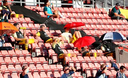 Arsenal substitute players holding umbrellas to shade from the sun respect social distancing during the English Premier League soccer match between Southampton FC and Arsenal FC in Southampton, Britain, 25 June 2020.