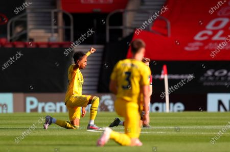 Arsenal's Pierre-Emerick Aubameyang (L) kneels down to make a stand against racism before the English Premier League soccer match between Southampton FC and Arsenal FC in Southampton, Britain, 25 June 2020.
