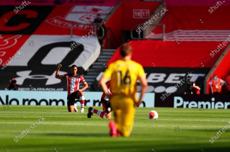 Southampton's Yan Valery (L) kneels down to make a stand against racism before the English Premier League soccer match between Southampton FC and Arsenal FC in Southampton, Britain, 25 June 2020.