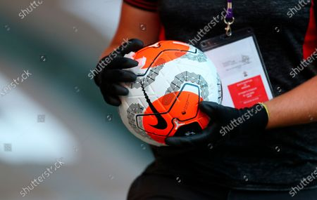 A staff member disinfects the official Nike match ball during the English Premier League soccer match between Southampton FC and Arsenal FC in Southampton, Britain, 25 June 2020.