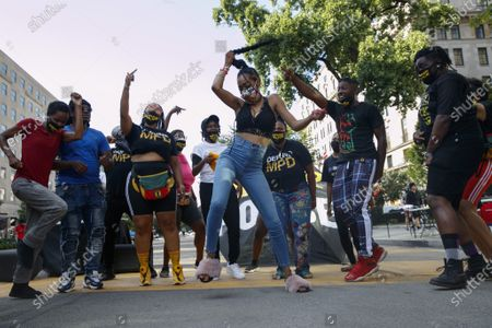Stock Picture of Tamia Washington, center, of Washington, dances while whipping her braid in a circle as she joins Black Lives Matter DC organizers and supporters in making a music video while on a section of 16th Street that's been renamed Black Lives Matter Plaza, in Washington, where protests continue over the death of George Floyd, a black man who was in police custody in Minneapolis. Floyd died after being restrained by Minneapolis police officers