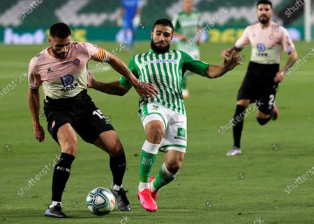Betis' Nabil Fekir (C) in action against Espanyol's David Lopez (L) during the Spanish La Liga soccer match between Real Betis and RCD Espanyol at Benito Villamarin stadium in Seville, southern Spain, 25 June 2020.