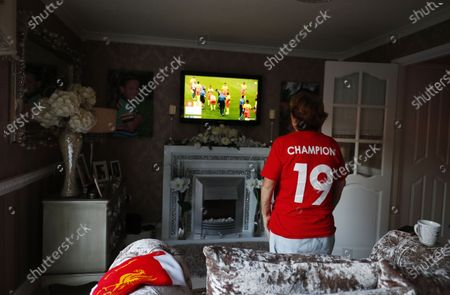 Liverpool supporter Emily Farley watches the Premier League match between Chelsea FC and Manchester City FC on a television screen inside her home in Liverpool, Britain, 25 June 2020. Liverpool FC could be crowned champions of the Premier League for the first time in three decades in the event that Manchester City were to fail to beat Chelsea. If City draw or lose, it would mathematically hand the English top league title to the Liverpudlian club tonight.