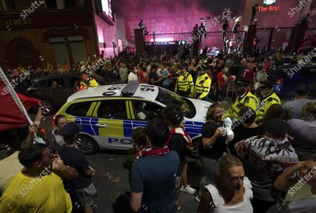 Police officers arrive as Liverpool supporters celebrate outside of Anfield Stadium in Liverpool, England, after Liverpool clinched the English Premier League title. Liverpool took the title after Manchester City failed to beat Chelsea on Wednesday evening