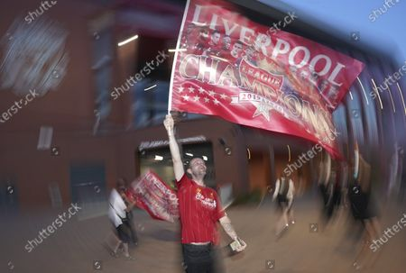 Stock Photo of Liverpool supporter celebrates outside Anfield Stadium in Liverpool, England, after hearing Chelsea had scored in the English Premier League soccer match between Chelsea and Manchester City. Liverpool will be crowned Premier League champions if Manchester City fail to beat Chelsea
