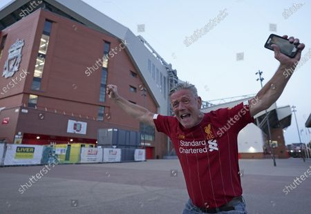 Liverpool supporter, Peter Fowler, celebrates outside Anfield Stadium in Liverpool, England, after hearing Chelsea had scored in the English Premier League soccer match between Chelsea and Manchester City. Liverpool will be crowned Premier League champions if Manchester City fail to beat Chelsea