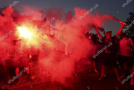 Liverpool supporters celebrates outside Anfield Stadium in Liverpool, England, after hearing Chelsea had scored in the English Premier League soccer match between Chelsea and Manchester City. Liverpool will be crowned Premier League champions if Manchester City fail to beat Chelsea