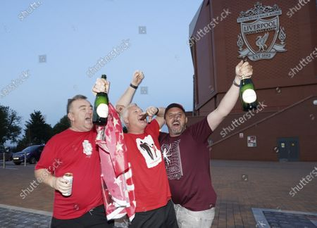 Liverpool supporters celebrate outside Anfield Stadium in Liverpool, England, after hearing Chelsea had scored in the English Premier League soccer match between Chelsea and Manchester City. Liverpool will be crowned Premier League champions if Manchester City fail to beat Chelsea