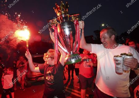 Liverpool supporters hold a replica Premier League trophy as they celebrate outside of Anfield Stadium in Liverpool, England, after Liverpool clinched the English Premier League title. Liverpool took the title after Manchester City failed to beat Chelsea on Wednesday evening