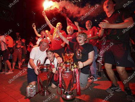 Liverpool supporters with replica Premier League and Champions League trophies as they celebrate outside of Anfield Stadium in Liverpool, England, after Liverpool clinched the English Premier League title. Liverpool took the title after Manchester City failed to beat Chelsea on Wednesday evening