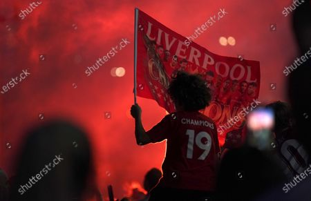 Liverpool supporters celebrate as they gather outside of Anfield Stadium in Liverpool, England, after Liverpool clinched the English Premier League title. Liverpool took the title after Manchester City failed to beat Chelsea on Wednesday evening