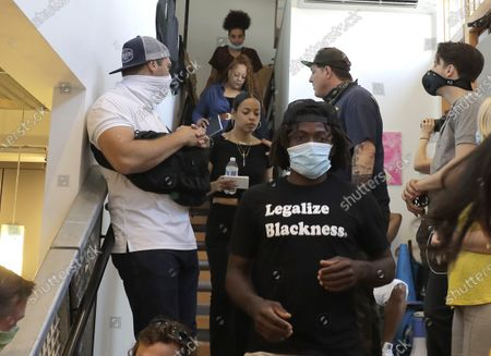Marcus Henderson, lower center, and Naudia Miller, center, of Black Collective Voices, arrive to speak, at a news conference in Seattle. Miller said the goal of protesters who have been active in the CHOP (Capitol Hill Occupied Protest) zone and elsewhere in the city since the death of George Floyd in Minneapolis is to dismantle systemic racism and to continue organizing until all of their demands are met