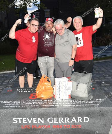Ecstatic Liverpool FC supporters celebrate next to a tribute plaque commemorating the team's former captain Steven Gerrard as they celebrate outside Anfield stadium in Liverpool, Britain, 25 June 2020. Liverpool have been crowned champions of the Premier League for the first time in three decades after Chelsea FC beat Manchester City FC 2-1. Man City's failure to win this crucial duel mathematically handed the English top league title to the Liverpudlian club led by German manager Juergen Klopp.