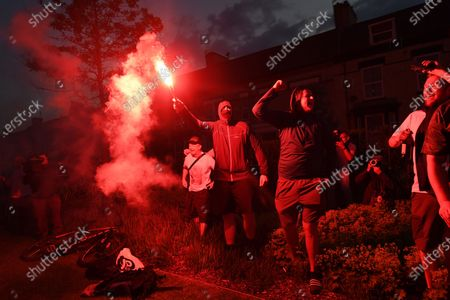 Ecstatic Liverpool FC supporters light up flares as they celebrate next to Anfield stadium in Liverpool, Britain, 25 June 2020. Liverpool have been crowned champions of the Premier League for the first time in three decades after Chelsea FC beat Manchester City FC 2-1. Man City's failure to win this crucial duel mathematically handed the English top league title to the Liverpudlian club led by German manager Juergen Klopp.