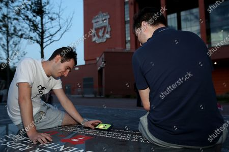 Liverpool fans watch the match between Chelsea and Manchester City outside Anfield