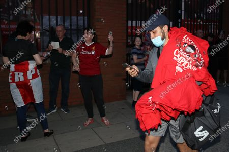 A street trader with merchandise as Liverpool fans outside Anfield celebrate winning the Premier League for the first time in 30 years after Chelsea beat Manchester City tonight ensuring Liverpool can no longer be overtaken on points.