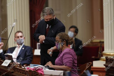 Sen. Holly Mitchell, D-Los Angeles, chair of the Senate Budget and Fiscal Review Committee, gets an elbow bump from Sen. Robert Hertzberg, D-Los Angeles, after the Senate approved the $202.1 billion state budget at the Capitol in Sacramento, Calif., . Mitchell carried the bills that made up the spending plan that covers the state's estimated $54.3 billion deficit brought on by the coronavirus. The Assembly is scheduled to vote on the budget Friday