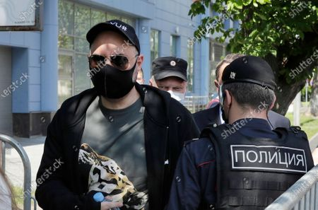 Russian film and theater director Kirill Serebrennikov, left, wearing a face mask to protect against coronavirus arrives for a court hearing at the Meshchansky court, in Moscow, Russia, . A court in Moscow is expected to deliver a verdict on Friday to the acclaimed theater director accused of embezzling state funds, in a case widely seen as politically motivated