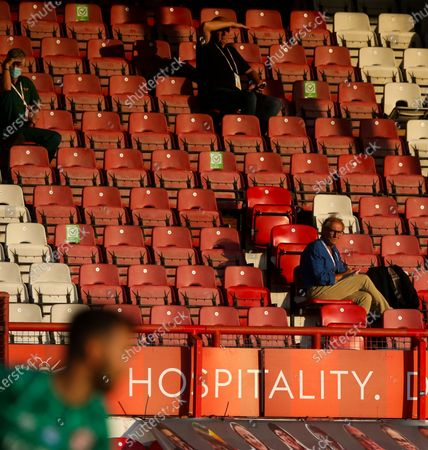 Socially distanced journalists watch the match - Goalkeeper David Raya of Brentford (L)