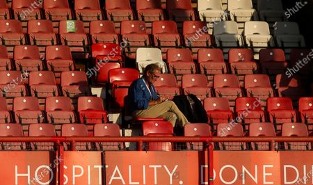 A journalist sits alone, social distancing in the stand