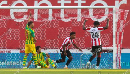 Ollie Watkins of Brentford (2nd R) looks over to the assistant referee as he scores the opening goal -  Tariqe Fosu of Brentford celebrates (R)